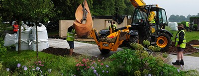 Sadie May team members lifting sculpture into garden