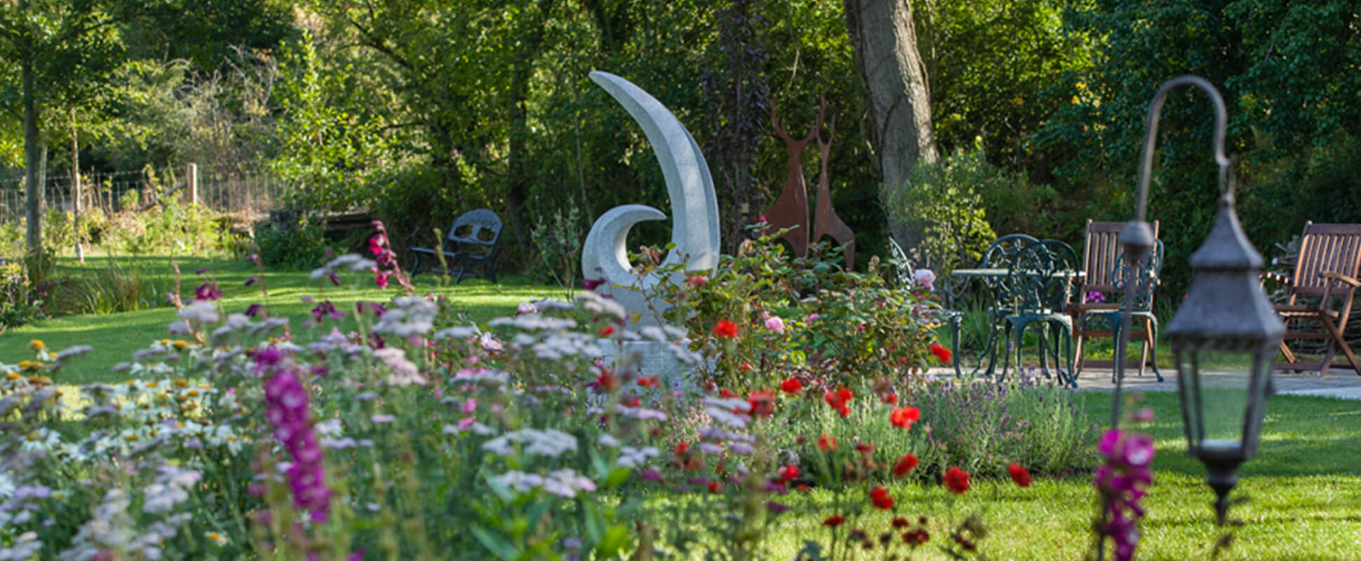 A garden featuring sculptures and garden furniture