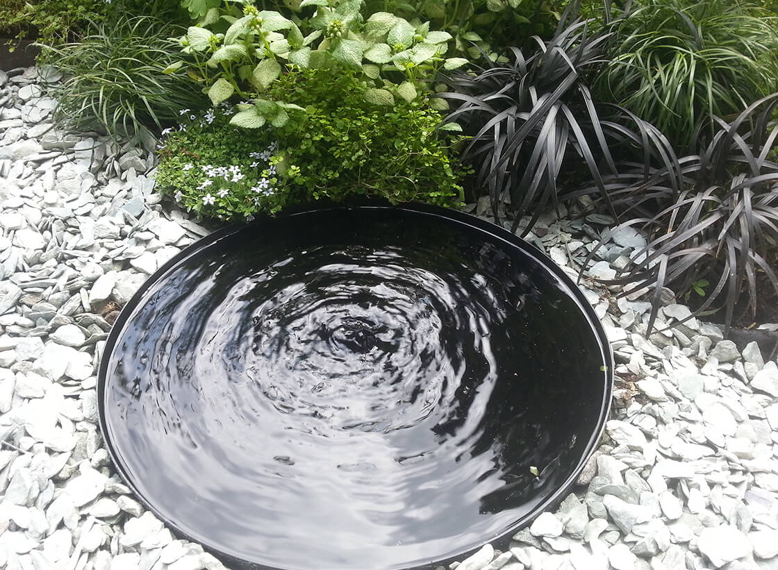A stylish water feature in a gravel garden