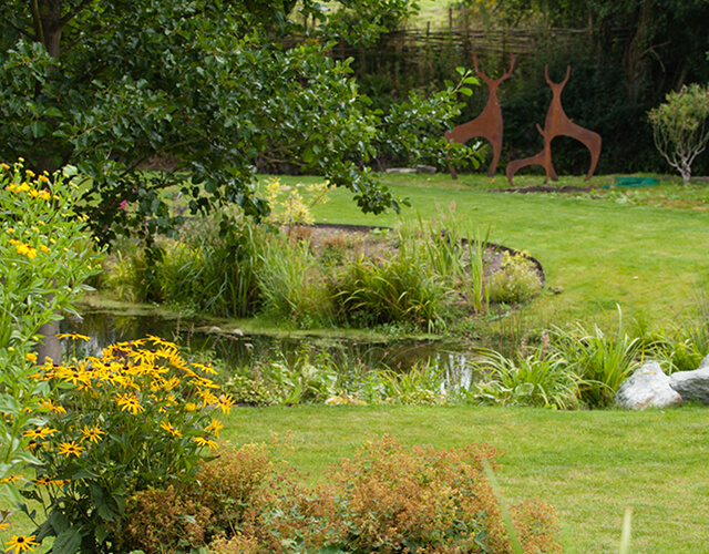 A garden with a pond and a family of deer sculptures